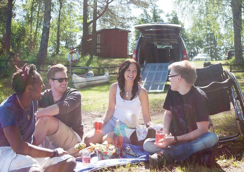 Fyra ungdomar på picnic, i bakgrunden bil med ramp.