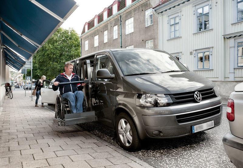 Minivan vid trottoar med utfälld sidolift.