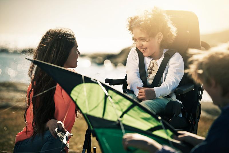 Flicka i ett Carony säte leker med kompisar.