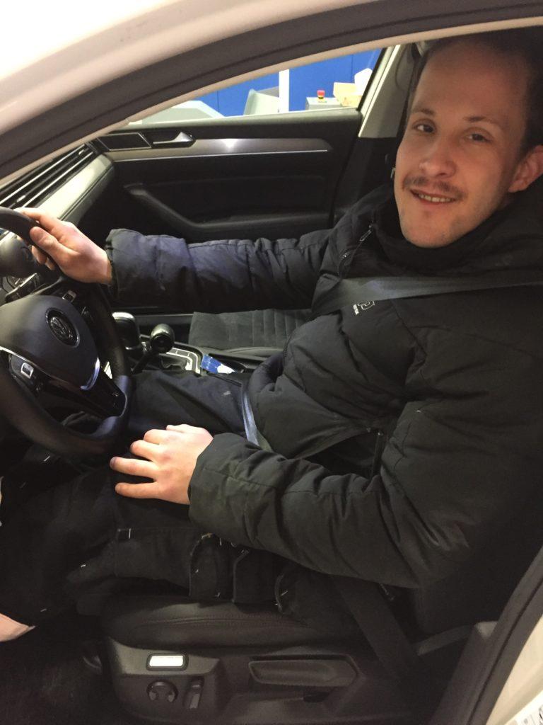 Martin sitter på förarplatsen i sin nya anpassade bil.